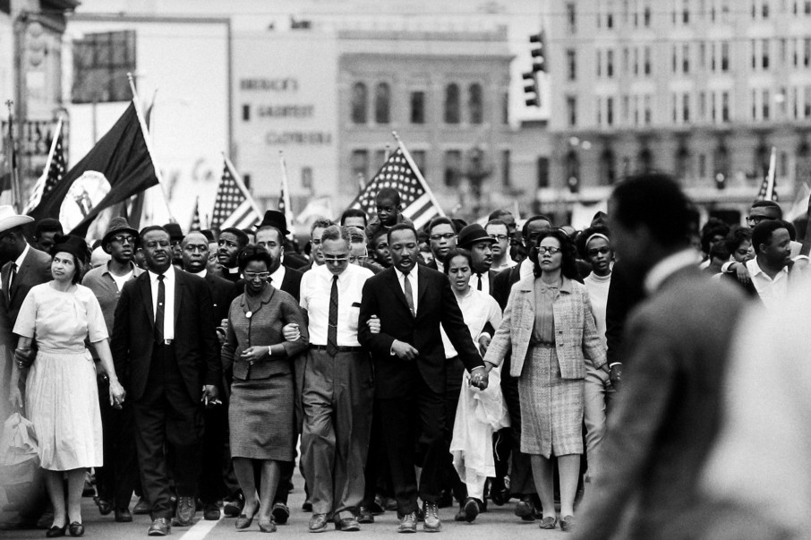Martin Luther King leads a large crowd of African American men, women and children filling the street as they march towards the camera. They are dressed in formal 60s clothing, singing or chanting, with arms linked or hodling hands. A few people further back in the crowd are carrying American flags.