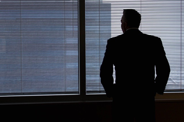 A man in a suit looks out of an office building window through venetian blinds at another office building
