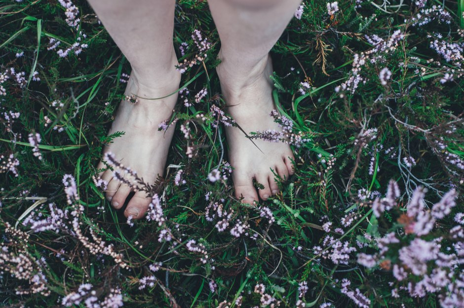 The bare feet of a child in the grass