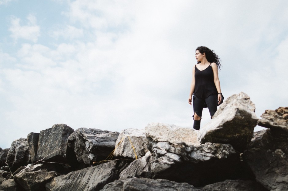 Young woman in torn black tights and sleeveless shirts stands on top of large boulders looking out