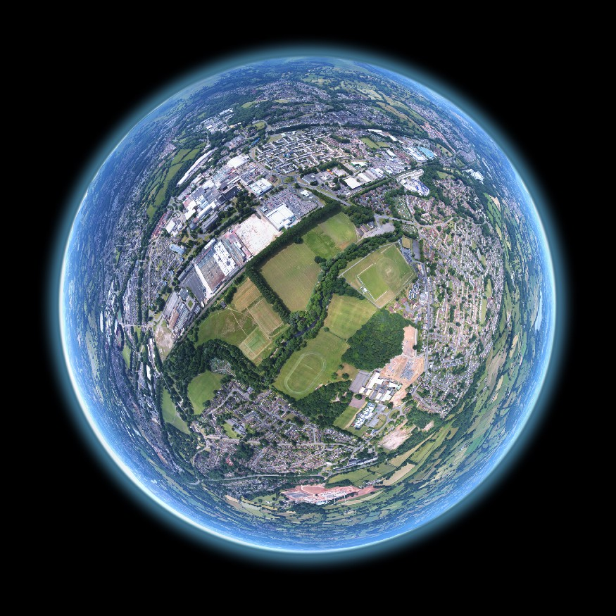Aerial fisheye of a suburban landscape superimposed on planet earth. Image by Louis Reed @ Unsplash.
