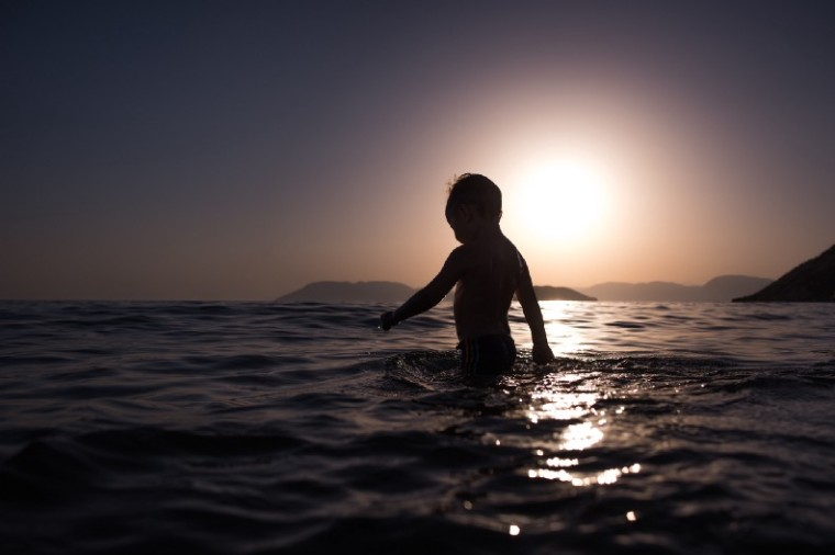 Child wading, silhouetted in sunlight