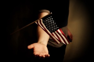 American flag waves over an outstretched hand.