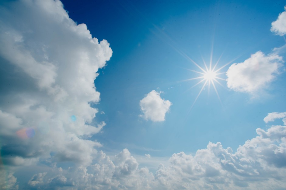 A star-like sun beams in a blue sky between clouds
