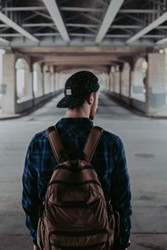 The back of a young man wearing a backpack and cap with the concrete and steel supports of a large building above him