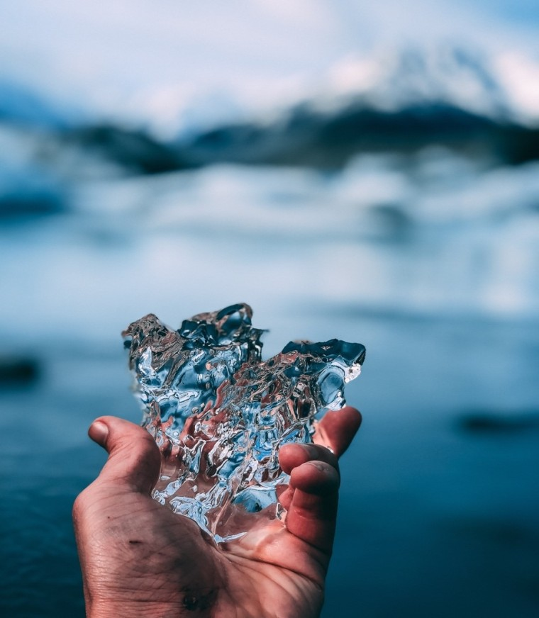A hand holds a rough, asymmetrical piece of ice which reflects the colors of a blurred snowy mountain landscape in the background.