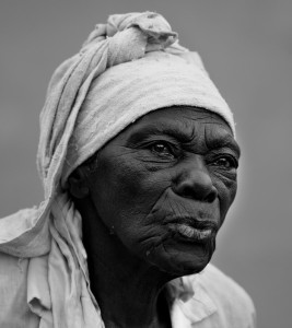 An elderly woman in a white turban purses her lips pensively as she seems to be watching some inner story