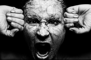A person is screaming. The face is covered with cracking mud, and the person's fists are pressing in one each side of their head