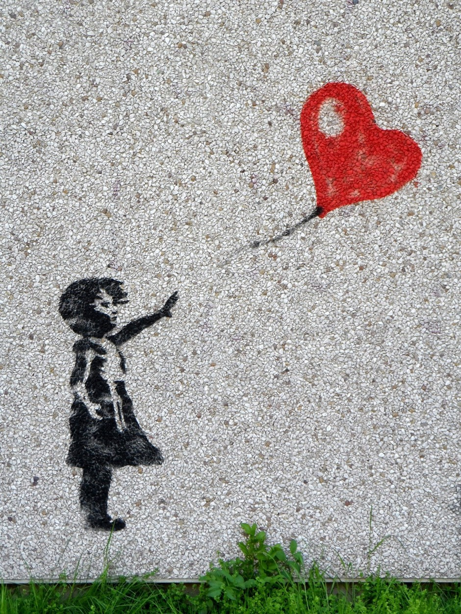 'Girl With Balloon' wall stencil by the artist Banksy showing a girl in black with her hand outstretched towards a a heart-shaped balloon flying just out of reach.