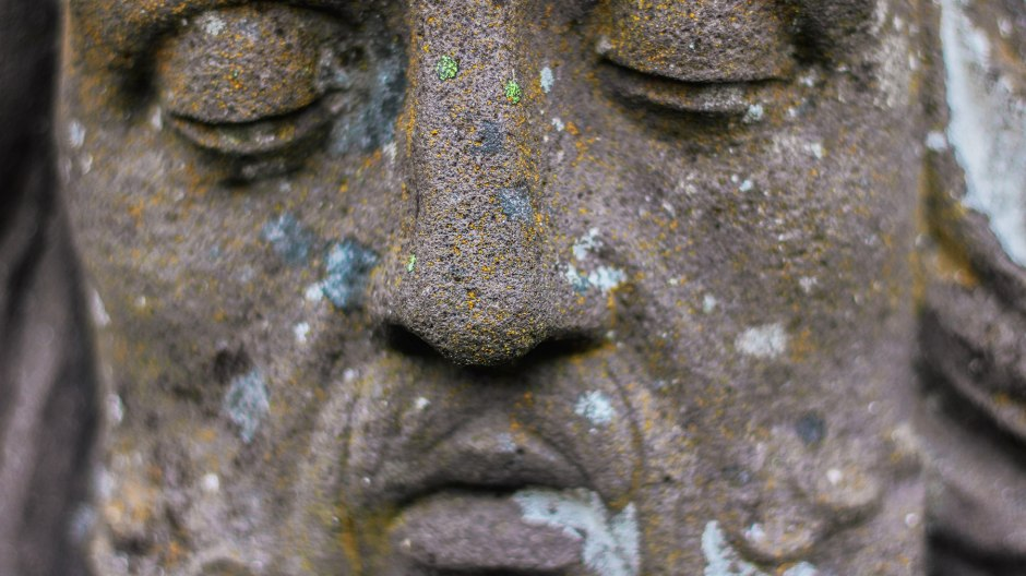 Close up of carved face of a man with closed eyes.