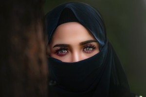 Young woman with eye makeup peers out from a black scarf that covers her hair and and the lower half of her face.