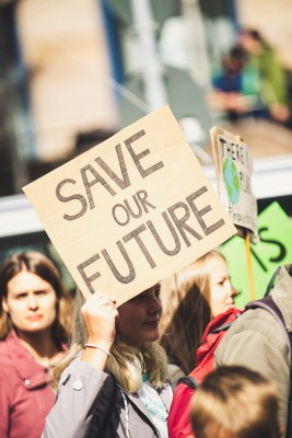 "A young woman at a demonstration holds a sign that says ""Save Our Future"""