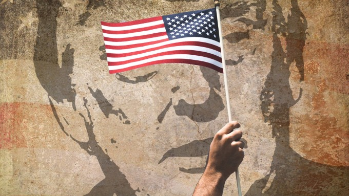 In front of a faded wall mural of Donald Trump with an American flag background, a real hand holds up a real flag