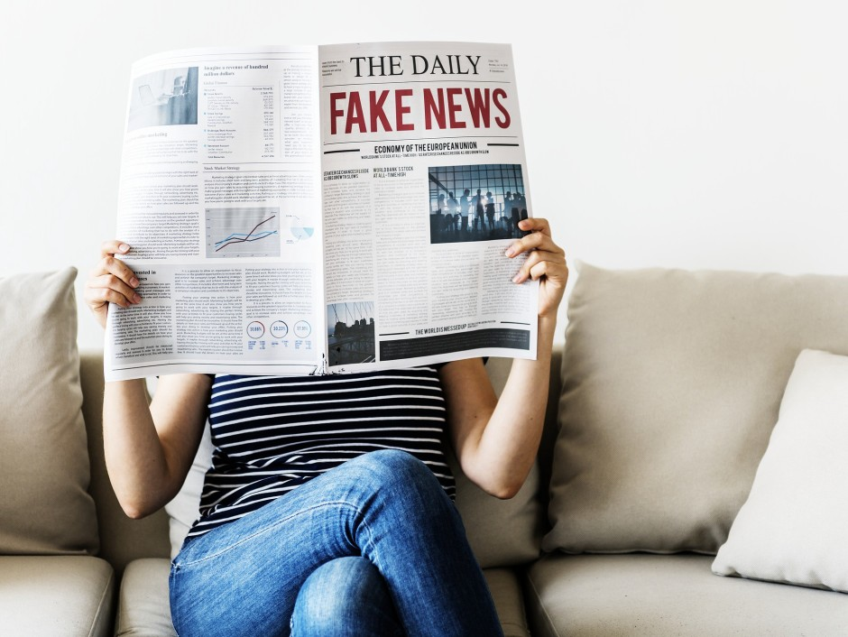 A woman sits on a couch reading a newspaper with the huge red headline 'FAKE NEWS'