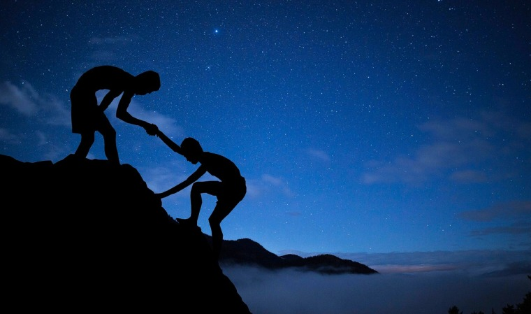 On a rocky mountain top at dusk or dawn, one boy helps another climb the last steps to the top