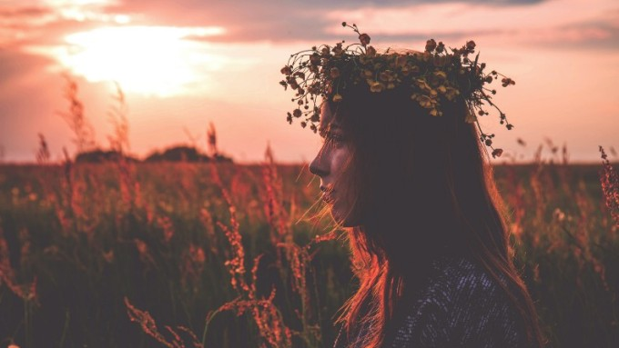 A woman stands in a field with the early evening sun on her face, wearing a wreath of grasses and small wildflowers