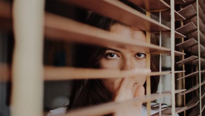 Woman peers through venetian blinds